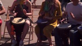 Frauen und Männer sitzen auf Holzstühlen und spielen afrikanische Instrumente, darbuka und djembe in der Straße, am Festival stock footage