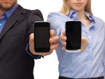 Frauen- und Mannhände mit Smartphones Stockfotos