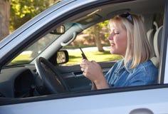 Frauen-Versenden von SMS-Nachrichten beim Antreiben Lizenzfreie Stockbilder