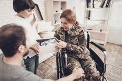 Frauen-Veteran im Rollstuhl-Heimkehr-Konzept stockbild
