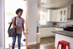 Frauen-Von der Arbeit nach Hause kommen und Öffnungs-Tür der Wohnung lizenzfreies stockbild