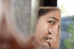 Frauen von mittlerem Alter betrachten den Spiegel, um das Gesichts-wr zu sehen Stockfoto