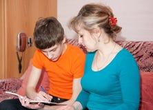 Mutter hilft ihrem Sohn, Hausarbeit vorzubereiten Lizenzfreie Stockfotografie
