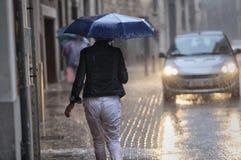 Frauen walkng unter dem tragenden Regenschirm des Regens Lizenzfreies Stockbild
