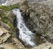 Frauen-Wanderer durch Wasserfall Stockbild