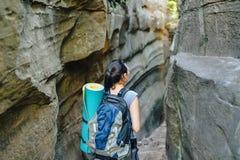 Frauen-Wanderer-Wanderer, der schmale Schlucht am Sommertag, Ansicht von der Rückseite erforscht Stockbild