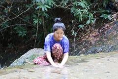 Frauen waschen das Gesicht hinter dem Wasserfall Stockbild