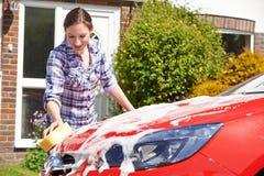 Frauen-waschendes Auto außerhalb des Hauses Lizenzfreie Stockfotos