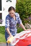 Frauen-waschendes Auto außerhalb des Hauses stockbild