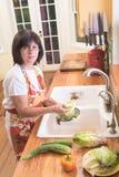 Frauen-waschendes Salat-Gemüse in der Küche Lizenzfreie Stockfotos
