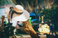 Frauen-weißer Hut durch Champagne Bottle an den Blumen Stockfoto