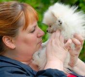 Frauen-Wekzeugspritze, zum mit einem weißen Pomeranian Welpen zu riechen Stockbild