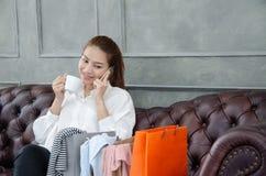 Frauen, welche die orange Einkaufstaschen glücklich tragen stockbilder