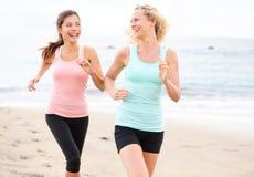 Frauen, welche die rüttelnde Ausbildung glücklich auf Strand laufen lassen Stockbild