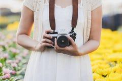 Frauen, welche die weißen Kleider, eine Kamera tragend tragen lizenzfreie stockfotos