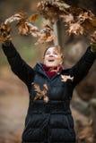 Frauen-werfende Blätter auf der Luft, das Leben genießend, Außenaufnahmen Lizenzfreies Stockbild