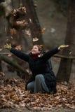 Frauen-werfende Blätter auf der Luft, das Leben genießend, Außenaufnahmen Stockfotos