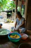 Frauen wickeln oben zylinderförmigen Klebreiskuchen ein. NHON  Lizenzfreie Stockbilder
