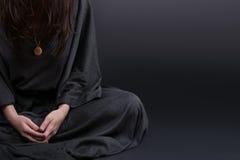 Frauenabbildung Beten Gebet kleidete in den Kleidungen einer Nonne auf grauem Studiohintergrund an Religions- und Hoffnungskonzep Stockbild