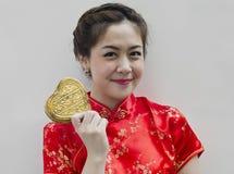 Frauenabnutzung cheongsam und goldenes Inneres der Holding Stockfoto