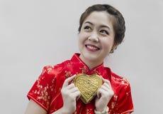 Frauenabnutzung cheongsam und goldenes Inneres der Holding Lizenzfreies Stockbild