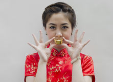 Frauenabnutzung cheongsam und Holdingchinesegold Stockfoto