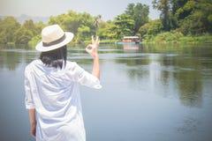 Frauenabnutzungshut und wei?es Hemd mit Stellung auf Holzbr?cke, macht sie vorw?rts schauend zum Fluss mit O.K.geste lizenzfreie stockfotos