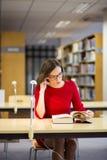 Frauenanfang, der fettes Buch mit Gläsern liest Stockfoto