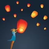 Frauenanfang eine rote chinesische Himmellaterne zum Himmel Lizenzfreie Stockbilder