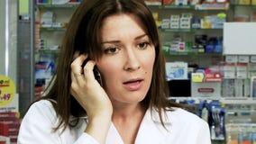 Frauenapotheker, der am Telefon kämpft stock video footage