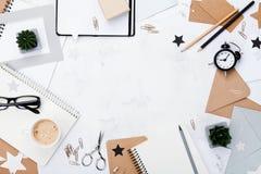 Frauenarbeitsschreibtisch mit Draufsicht des Kaffees, des Bürozubehörs, des Weckers und des sauberen Notizbuches Flache Lage Kopi Stockbilder