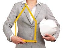 Frauenarchitekt, der ein Meter und einen Sturzhelm hält Lizenzfreie Stockbilder