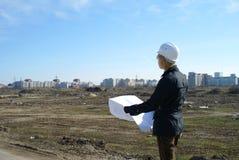 Frauenarchitekt mit hartem Hut an der Baustelle Stockbild