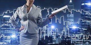 Frauenarchitekt oder -ingenieur, die Baukonzept darstellen und in der Hand Dokumente verwahren Lizenzfreie Stockbilder