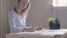 Frauenarchitekten, sitzend am Schreibtisch im Büro mit Bauplänen stock video
