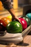 Frauenarm und -Bowlingkugel Stockfotos