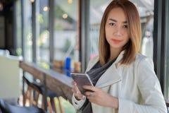 Frauenasiat, der Telefon für online kaufen und das Nennen mit cel verwendet lizenzfreie stockfotografie