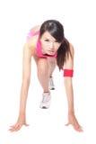 Frauenathlet in der Stellung betriebsbereit zu laufen Stockbilder
