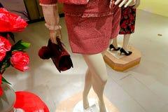 Frauenattrappe mit roter Tasche und Blume Stockfoto