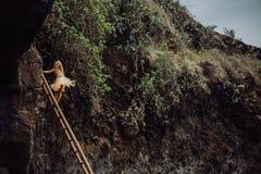 Frauenaufenthalt auf Treppe auf dem tropischen Strandschwarz-Sandkleid gelb stockbild
