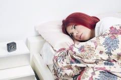 Frauenaufwachen, liegend auf dem Bett wach stockfotografie
