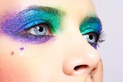 Frauenaugen mit glänzendem Feiertag spangled Make-up Stockfotografie