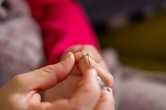 Frauenausschnitt und Knoten eines Fadens auf einer Nadel lizenzfreies stockfoto
