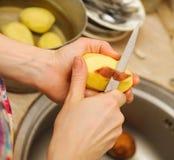 Frauenausschnitt, zum von Kartoffeln abzuziehen Bereiten Sie Nahrung zu Stockfotos