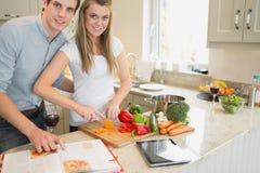 Frauenausschnittgemüse mit dem Mann, der das Kochenbuch liest Lizenzfreies Stockbild