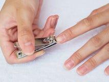 Frauenausschnittnägel unter Verwendung des Nagelscherers auf weißem Hintergrund heal stockfoto
