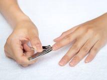 Frauenausschnittnägel unter Verwendung des Nagelscherers auf weißem Hintergrund heal stockfotografie