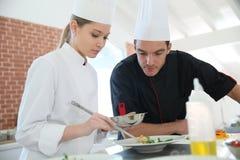 Frauenauszubildender im Kochkurs mit Chef Stockbild