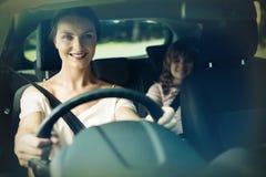 Frauenautofahren während Tochter, die im Rücksitze des Autos sitzt lizenzfreies stockbild