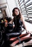 Frauenautorennläufer in der ledernen Klage, die einen Sturzhelm hält lizenzfreies stockfoto